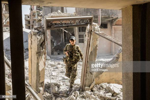 Syrian democratic forces fighter walks through rubbles in Raqqa SDF fighters are searching the ruined houses for Islamic State group jihadists The...
