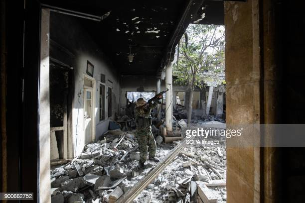 Syrian democratic forces fighter walks through rubbles in Raqqa SDF fighters are searching the ruined houses The Syrian civil war has been carried on...