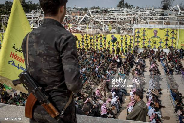 Syrian Democratic Forces fighter watches over guests attending the SDF victory ceremony announcing the defeat of ISIL in Baghouz held at Omer Oil...