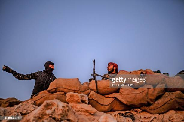 Syrian Democratic Forces fighters keep position on a hilltop near the embattled village of Baghouz in Syria's northern Deir Ezzor province on...