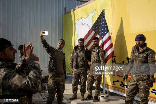 Syrian Democratic Forces fighters pose for a photo with the American flag on stage after a SDF victory ceremony announcing the defeat of ISIL in...