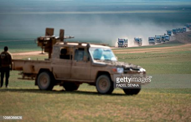 TOPSHOT Syrian Democratic Forces fighters stand guard as a convoy of trucks transports civilians fleeing the battered Islamic Stateheld holdout of...