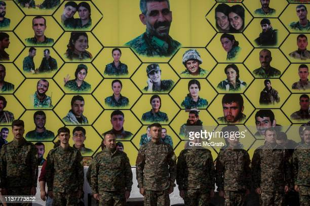 Syrian Democratic Forces fighters stand in front of a board showing portraits of fighters killed in battle during a SDF victory ceremony announcing...