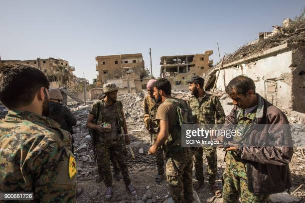 Syrian democratic forces fighters walks through rubbles in Raqqa They are searching for Islamic State group jihadists in the ruined houses The Syrian...