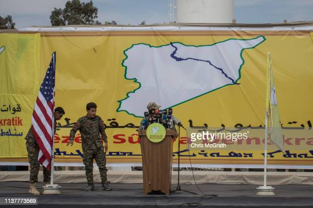 Syrian Democratic Forces members place an American flag on stage ahead of the SDF victory ceremony announcing the defeat of ISIL in Baghouz held at...
