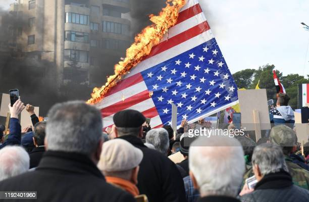 Syrian demonstrators burn the US flag as they gather in the central Saadallah al-Jabiri square in the northern Syrian city of Aleppo on January 7 to...