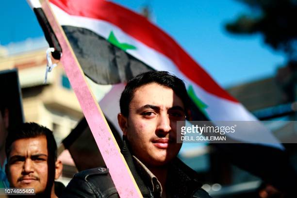 TOPSHOT Syrian demonstrators wave the national flag during a demonstration in the northeastern Syrian Kurdishmajority city of Qamishli on December 23...