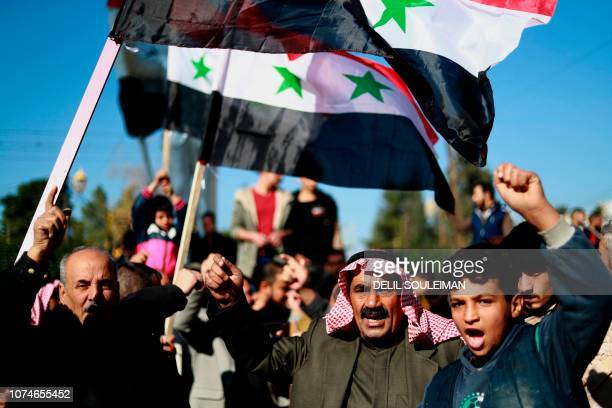 Syrian demonstrators wave the national flag during a demonstration in the northeastern Syrian Kurdishmajority city of Qamishli on December 23 asking...