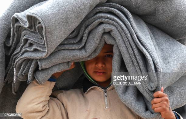 A Syrian displaced boy carries blankets over his head inside the Internallly Displaced Persons camp of alHol in alHasakeh governorate in northeastern...