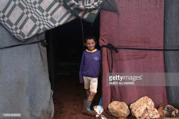 A Syrian displaced child poses for a photograph in a flooded refugee camp in the Idlib countryside northwestern Syria on October 25 2018 Heavy rains...