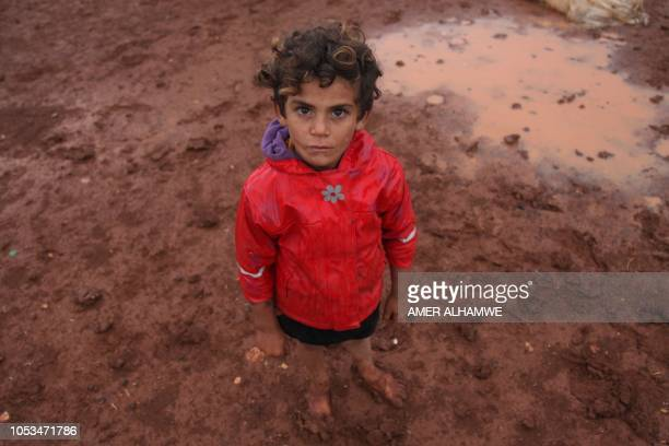 Syrian displaced child poses for a photograph in a flooded refugee camp in the Idlib countryside northwestern Syria on October 25 2018 Heavy rains...