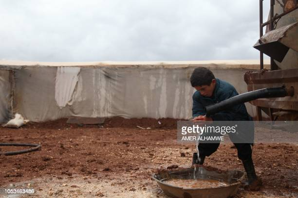 A Syrian displaced child washes his hands in a flooded refugee camp in the Idlib countryside northwestern Syria on October 25 2018 Heavy rains hit...
