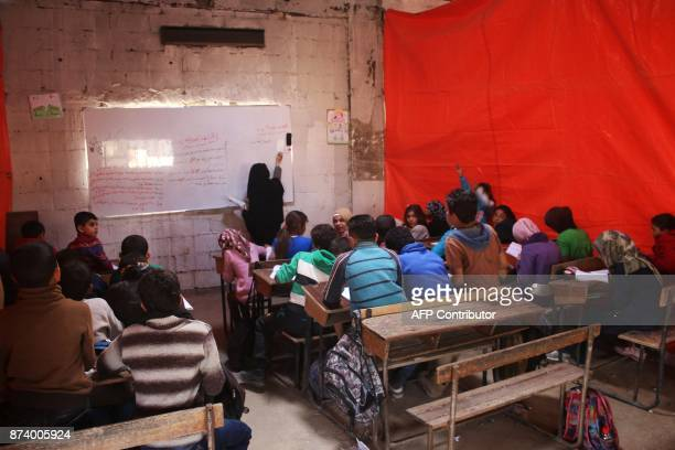 TOPSHOT Syrian displaced children attend a class at a makeshift school in a rebelheld area of the southern city of Daraa on November 14 2017 / AFP...