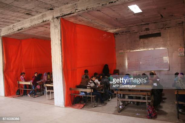 Syrian displaced children attend a class at a makeshift school in a rebelheld area of the southern city of Daraa on November 14 2017 / AFP PHOTO /...