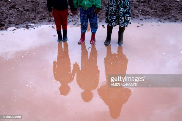 TOPSHOT Syrian displaced children pose for a photograph in a flooded refugee camp in the Idlib countryside northwestern Syria on October 25 2018...