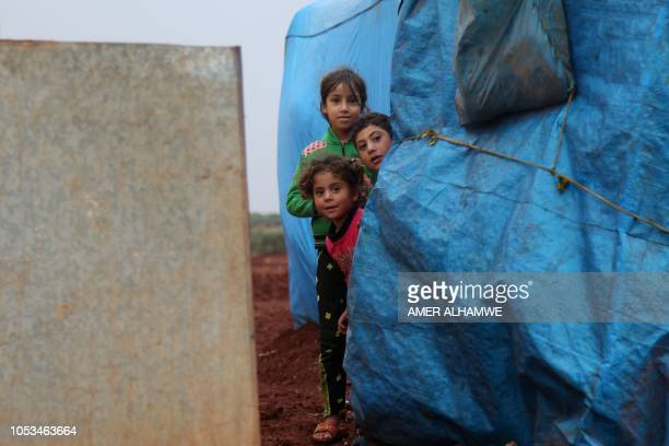 Syrian displaced children pose for a photograph in a flooded refugee camp in the Idlib countryside northwestern Syria on October 25 2018 Heavy rains...