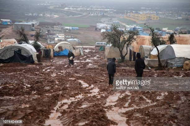 TOPSHOT Syrian displaced people walk in a flooded camp near Kah in the Idlib province northeastern Syria on December 19 2018