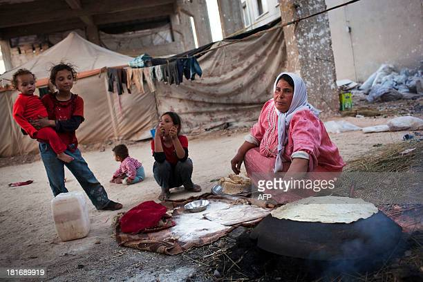 Syrian displaced woman prepares bread in an abandoned factory in the Sheikh Najjar industrial zone near Syria's northern city of Aleppo on September...