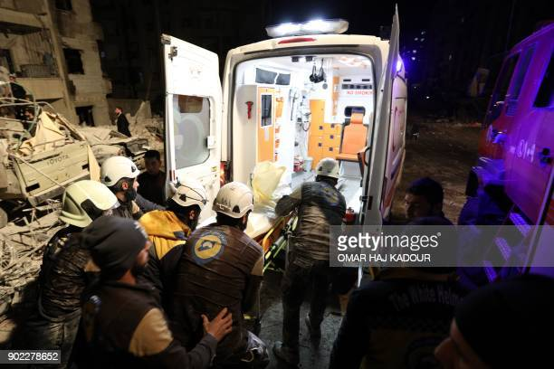 Syrian emergency personnel carry a victim into an ambulance following an explosion at a base for Asian jihadists in a rebelheld area of the...