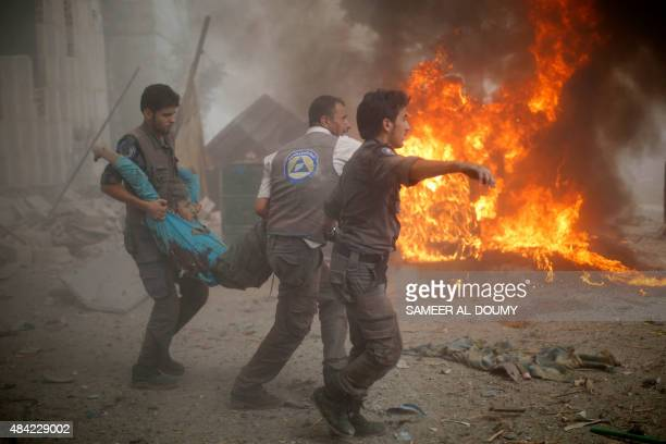 Syrian emergency personnel carry a wounded man following air strikes by Syrian government forces on a marketplace in the rebel-held area of Douma,...