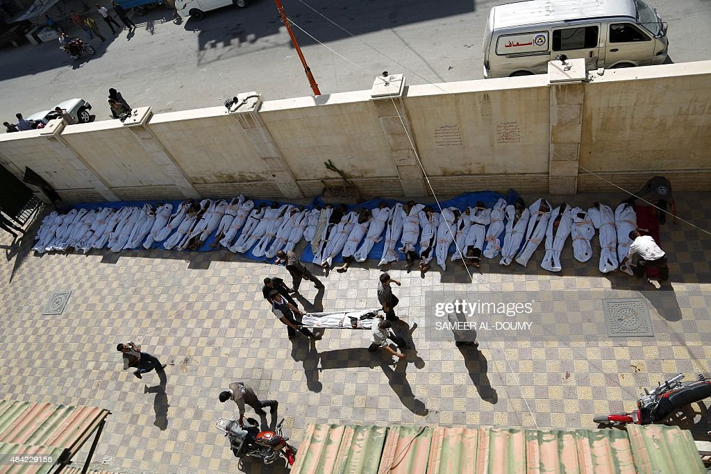 Syrian emergency personnel gather around dead bodies wrapped in shrouds following air strikes by Syrian government forces on a marketplace in the rebel-held area of Douma, east of the capital Damascus, on August 16, 2015. At least 82 people were killed and 250 people were injured, with the death toll -most of them civilians- likely to rise as many of the wounded were in serious condition, the Syrian Observatory for Human Rights said.