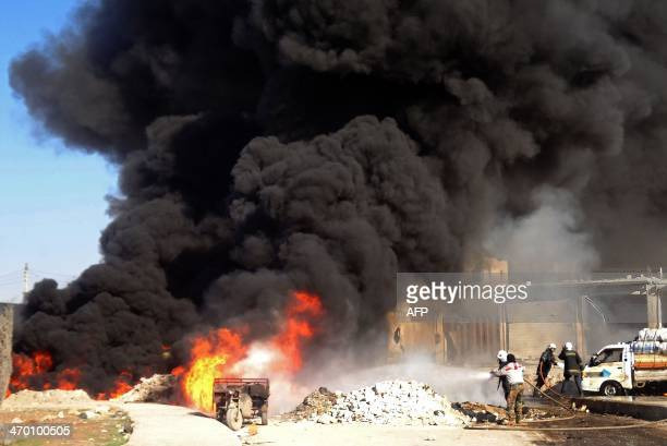 Syrian emergency personnel work at the site of a reported barrel bomb attack by government forces on February 18 2014 in the northern Syrian city of...