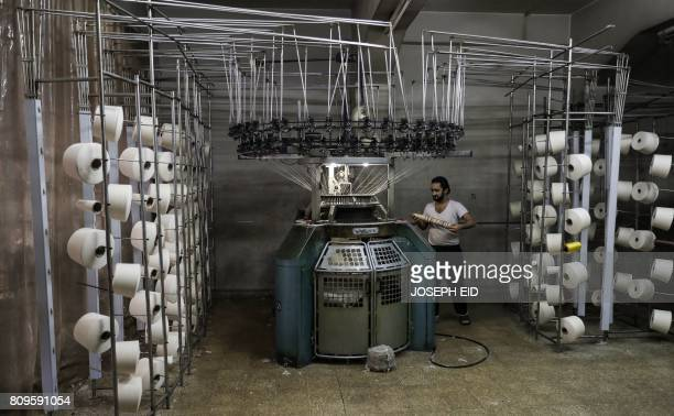 A Syrian employee works at a textile factory in Aleppo's Kallase neighbourhood on July 5 2017 / AFP PHOTO / JOSEPH EID