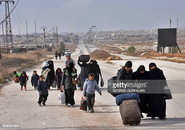 TOPSHOT Syrian families fleeing from various eastern districts of Aleppo carry their belongings on November 29 2016 in the governmentheld eastern...