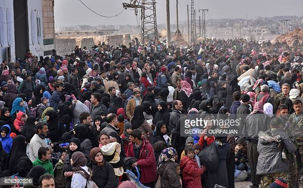 Syrian families fleeing from various eastern districts of Aleppo queue to get onto governmental buses on November 29 2016 in the governmentheld...