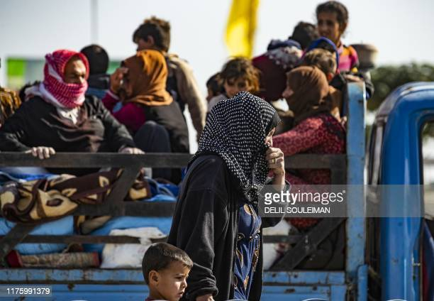 Syrian families fleeing the battle zone between Turkeyled forces and Kurdish fighters from the Syrian Democratic Forces in and around the northern...