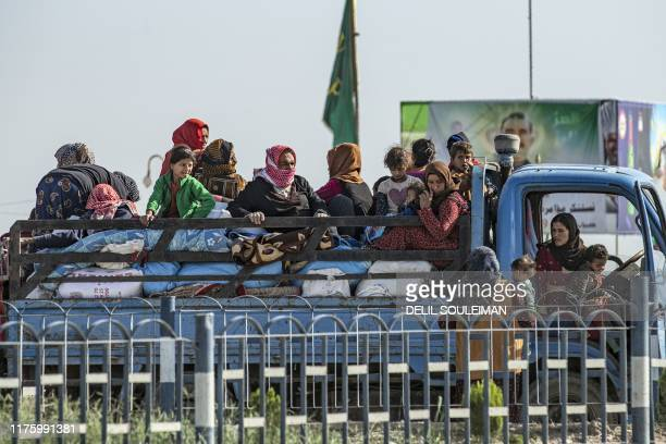 Syrian families fleeing the battle zone between Turkey-led forces and Kurdish fighters from the Syrian Democratic Forces in and around the northern...