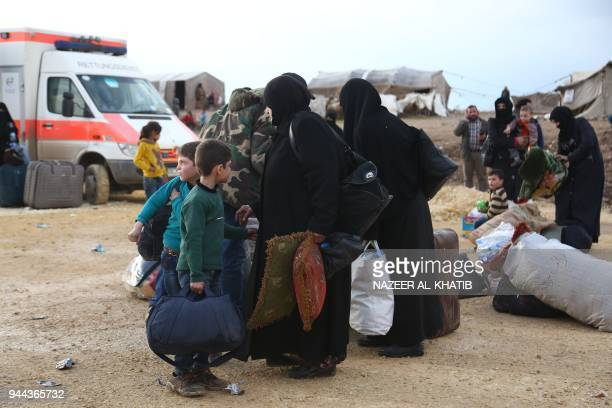 Syrian families gather at a camp for displaced people after buses carrying Jaish alIslam fighters and their families from their former rebel bastion...