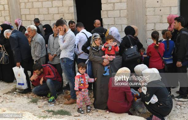 Syrian families gather at the Abu Duhur crossing on the eastern edge of Syria's Idlib province on October 23 2018 Civilians are coming from rebelheld...
