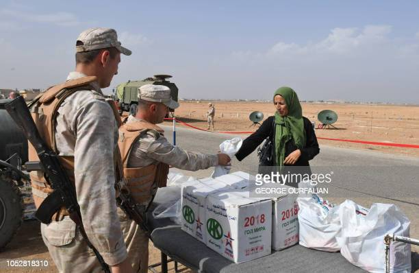 Syrian families receive aid from Russian soldiers at the Abu Duhur crossing on the eastern edge of Idlib province on October 23 2018 Civilians are...
