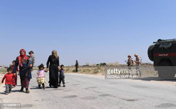 Syrian families walk as members of Russian and Syrian forces stand guard at the Abu Duhur crossing on the eastern edge of Idlib province on August 20...