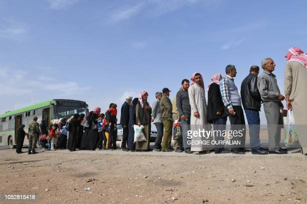 Syrian families walk as members of Russian and Syrian forces stand guard at the Abu Duhur crossing on the eastern edge of Syria's Idlib province on...