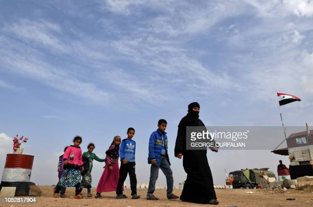 TOPSHOT Syrian families walk as members of Russian and Syrian forces stand guard at the Abu Duhur crossing on the eastern edge of Syria's Idlib...