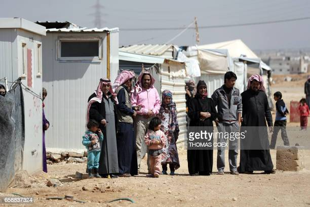 Syrian families watch during a visit to the Zaatari refugee camp which shelters some 80000 Syrian refugees on the Jordanian border with warravaged...