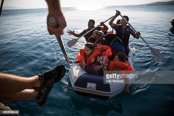 Syrian family arrive in an inflatable dinghy at Kos ferry port after the crossing from Turkey on August 30 2015 in Kos Greece Migrants from many...