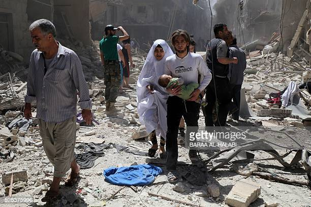 Syrian family walks amid the rubble of destroyed buildings following a reported airstrike on April 28 2016 in the Bustan alQasr rebelheld district of...
