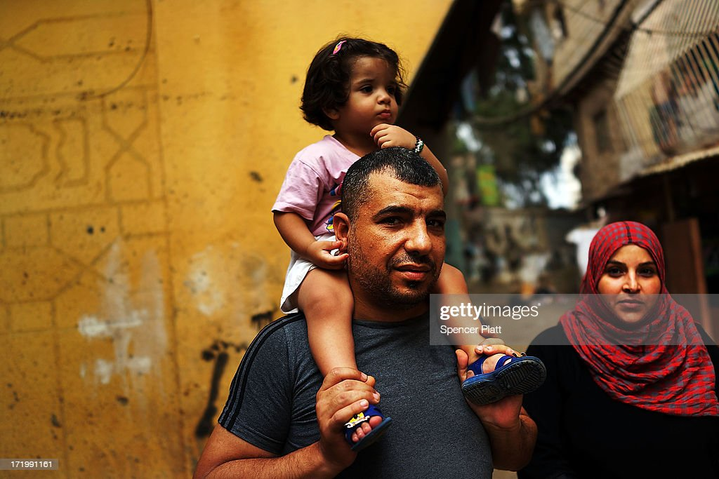 A Syrian family who recently fled Qusayr, Syria stand in a poor neighborhood with a high concentration of Syrian refugees on June 30, 2013 in Beirut, Lebanon. Currently the Lebanese government officially hosts 546,000 Syrians with an estimated additional 500,000 who have not registered with the United Nations. Lebanon, a country of only 4 million people, is now home to the largest number of Syrian refugees who have fled the conflict. The situation is beginning to put a huge social and political strains on Lebanon as there is currently no end in sight to the war in Syria.