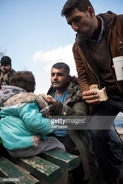 Syrian father feeding daughter on Lesbos, Greece