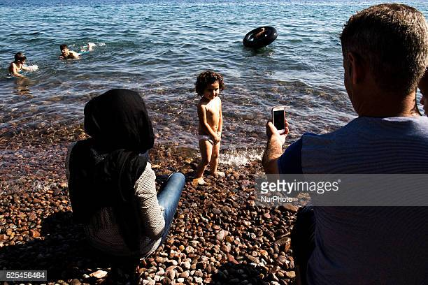 A syrian father takes a photograph of his daughter with his celphone after they arrived in Sikaminies coast of the Greek island Lesvos Greece comming...
