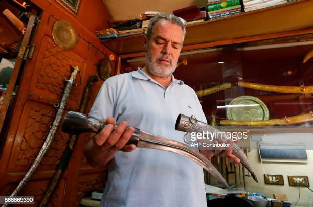 Syrian Fayad al-Sioufi looks at a dagger made of Damascus steel at his shop in the Syrian capital on May 31, 2017. / AFP PHOTO / Louai Beshara