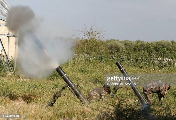 TOPSHOT Syrian fighters from the Turkishbacked Hamza faction fire a mortar from Syria's rebelheld Aleppo province toward regimeheld areas on May 9...