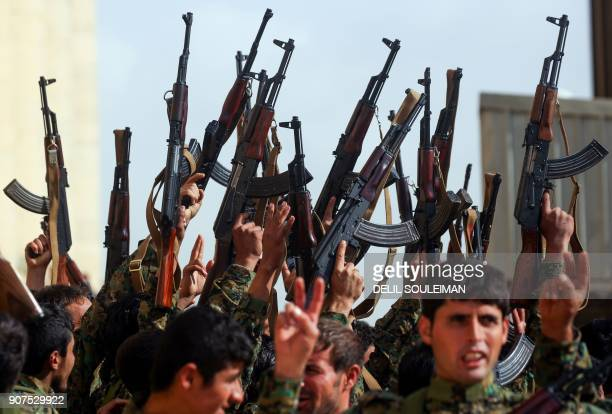 Syrian fighters hold up their weapons during their graduation ceremony near Syria's northeastern city of Hasakeh on January 20 at the end of a US-led...