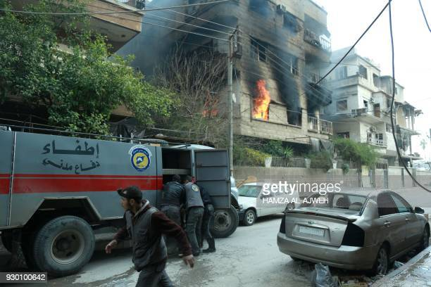 Syrian firefighters use a hose to extinguish fire following Syrian government shelling on the town of Douma in the rebelheld enclave of Eastern...