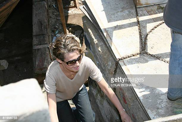 Syrian First Lady Asma alAssad climbs a ladder as she visits a replica of a Phoenician ship being built on the Syrian island of Arwad some 3 kms off...