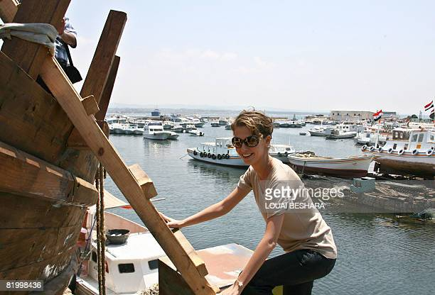 Syrian First Lady Asma alAssad is seen on a wooden ladder as climbs onto a replica of a Phoenician ship being built on the Syrian island of Arwad...