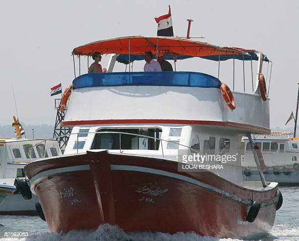 Syrian First Lady Asma alAssad rides on a boat following a visit to a replica of a Phoenician ship being built on the Syrian island of Arwad some 3...